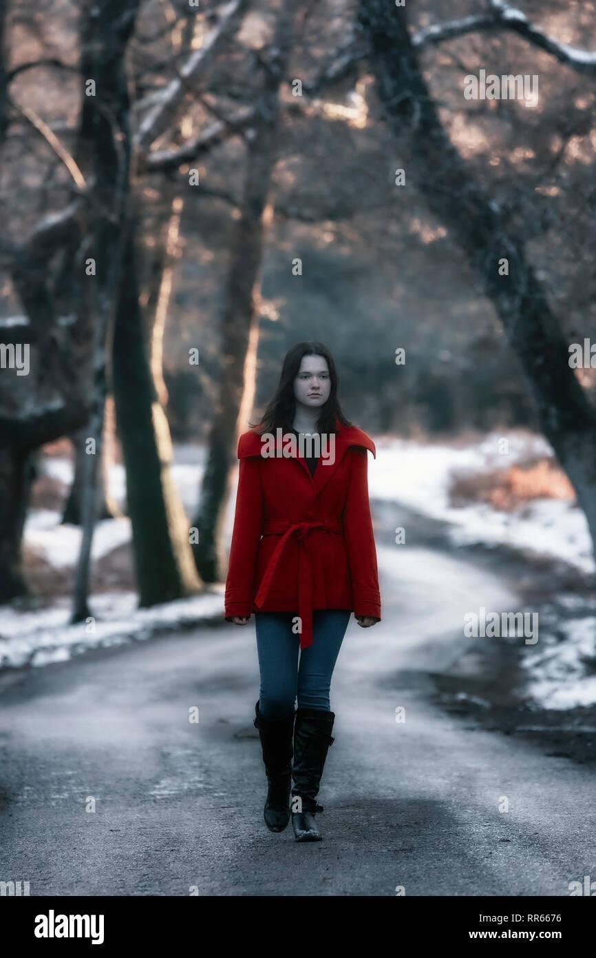 Une jeune femme avec un manteau rouge marchant le long d'une petite route dans une forêt hiver avec de la neige Banque D'Images