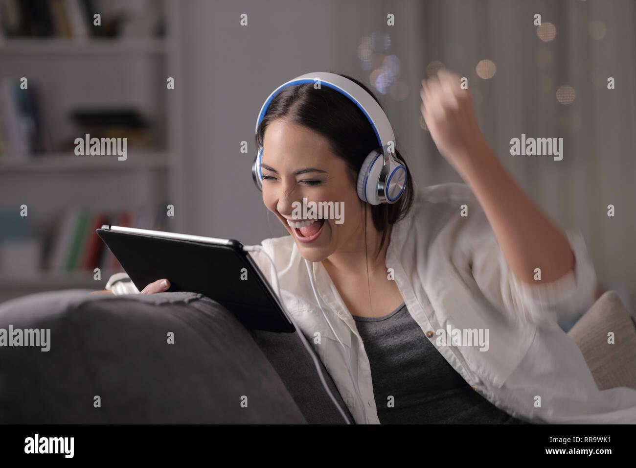 Excited woman écoute et regarde media sur tablet assis sur un canapé dans la nuit à la maison Banque D'Images
