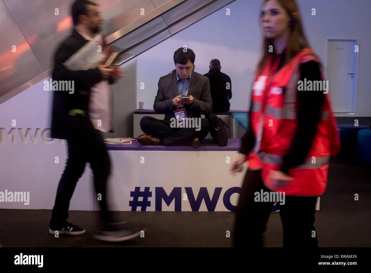 Barcelone, Catalogne, Espagne. Feb 25, 2019. Un préposé vérifie son téléphone mobile pendant le jour de l'ouverture de la GSMA Mobile World Congress 2019 à Barcelone, l'événement mondial le plus important sur la communication à partir d'appareils mobiles apportant togeteher les principales entreprises et les derniers développements dans le secteur. Crédit: Jordi Boixareu/ZUMA/Alamy Fil Live News Banque D'Images