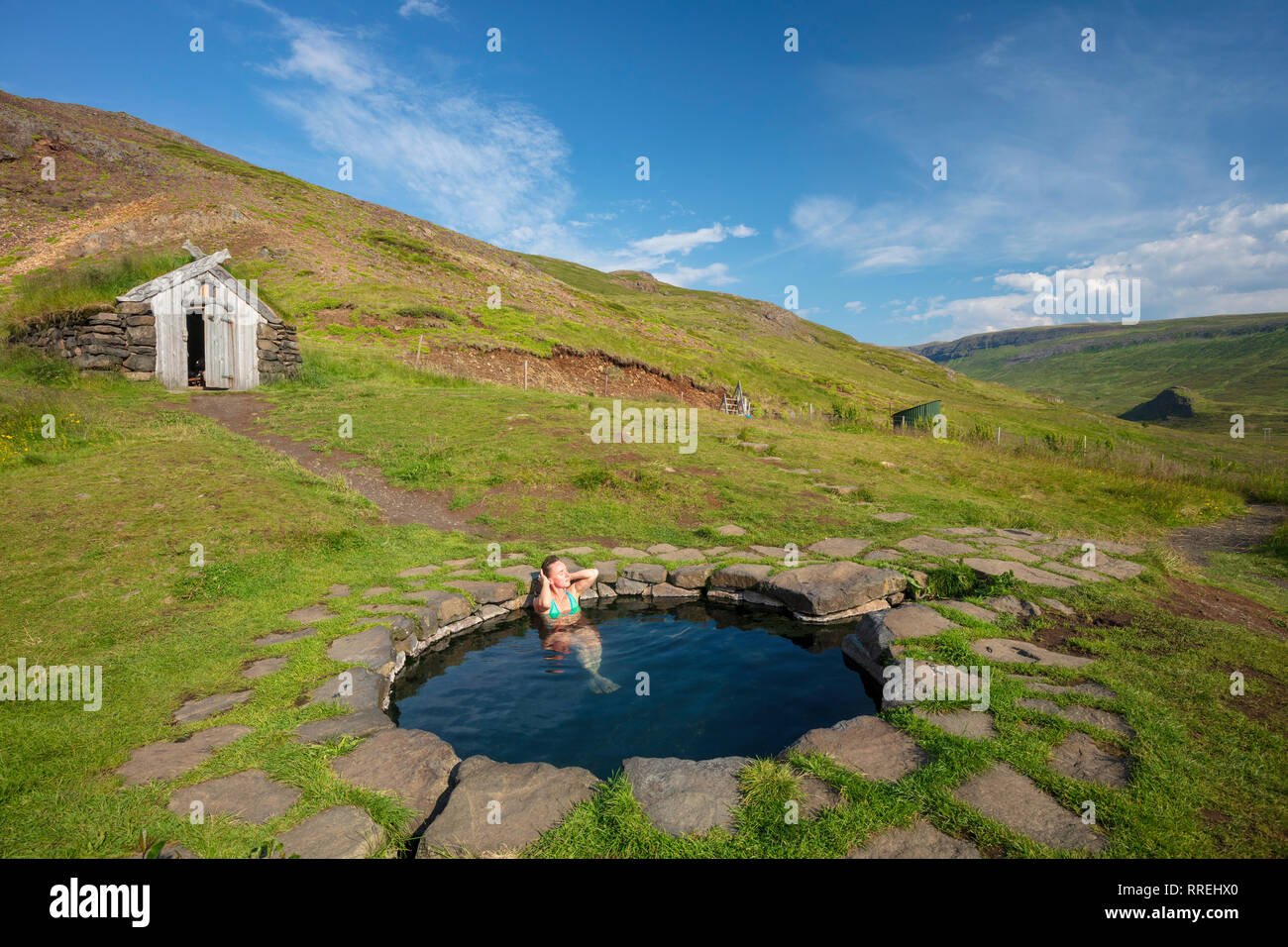 Woman bathing in Gudrunarlaug piscine géothermique. Laugar, Islande de l'ouest, Sælingsdalur. Banque D'Images