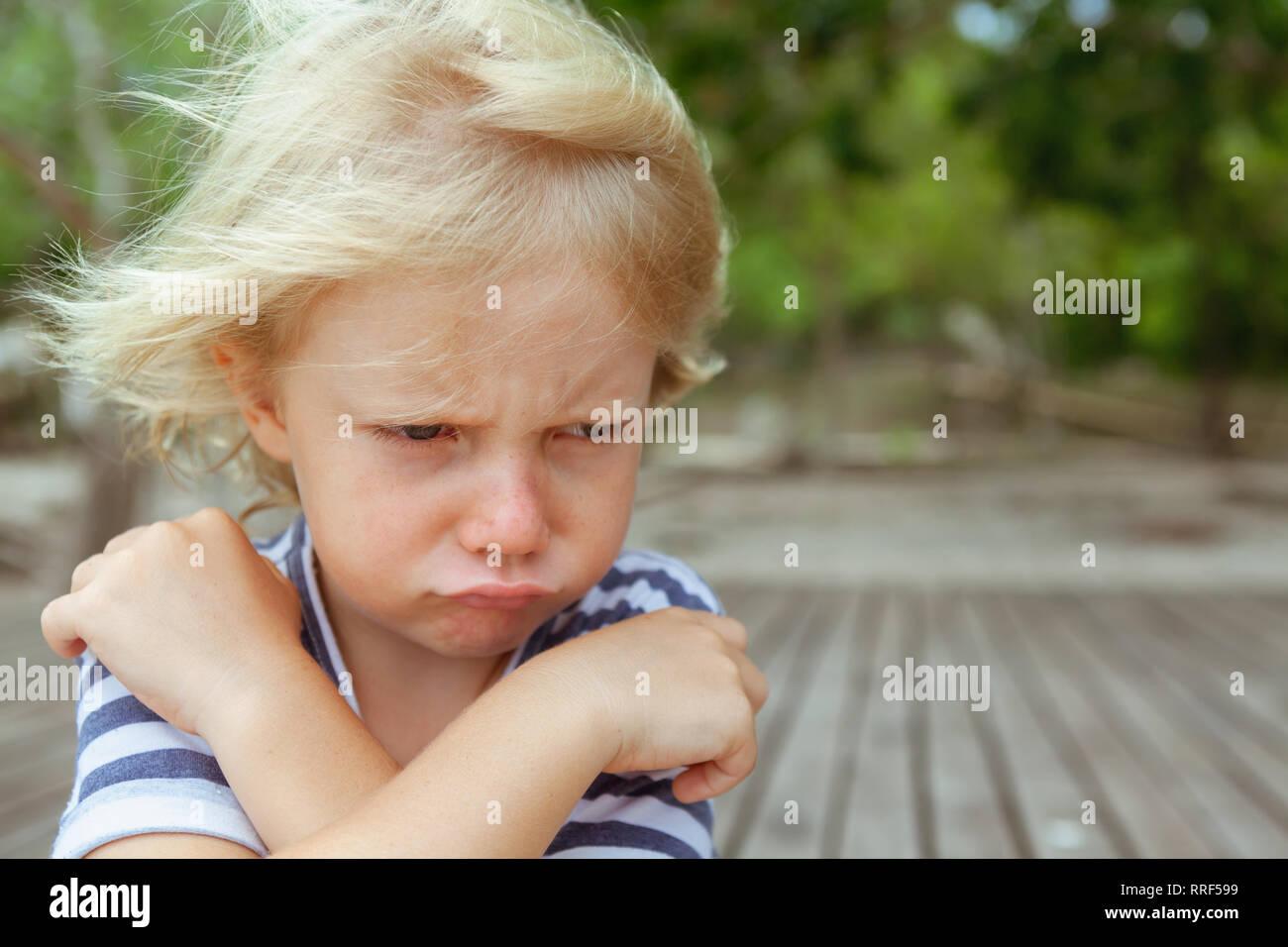 Face portrait de contrarié et mécontent caucasian kid avec bras croisés. Concept de l'enfant en colère et pour les relations familiales, les questions des problèmes sociaux Banque D'Images