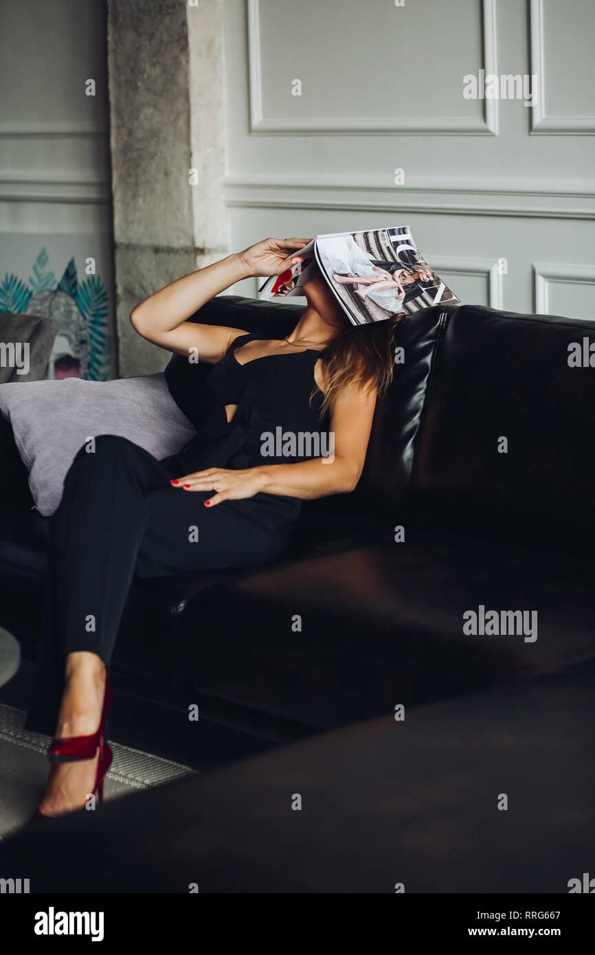 Tired woman sitting on couch et mettre magazine sur la tête. Photo Stock
