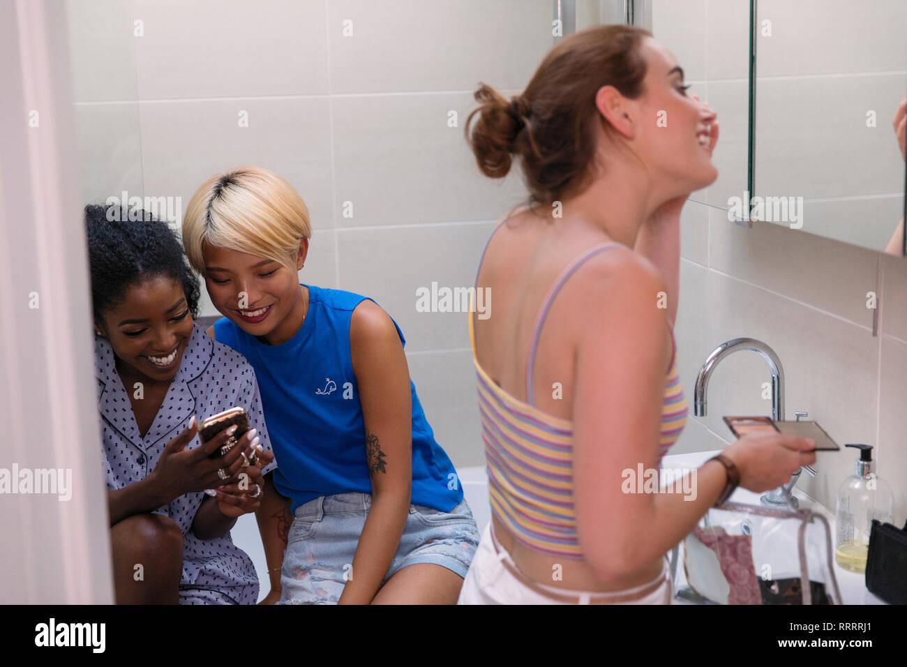 Les jeunes femmes colocataires à l'aide de smart phone et se préparer, appliquant le maquillage dans l'appartement salle de bains Banque D'Images