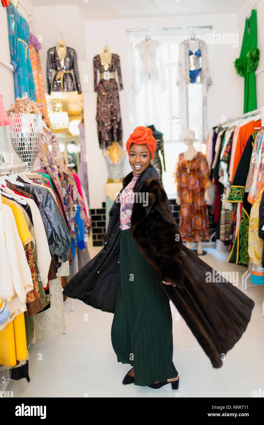 Portrait confiant, élégante jeune femme essayant sur manteau de fourrure in clothing store Banque D'Images