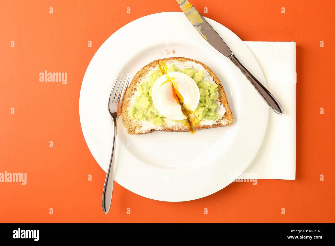 L'avocat de manger sur des toasts avec des oeufs pochés dans un café. Table de couleurs corail vivant. Photo Stock