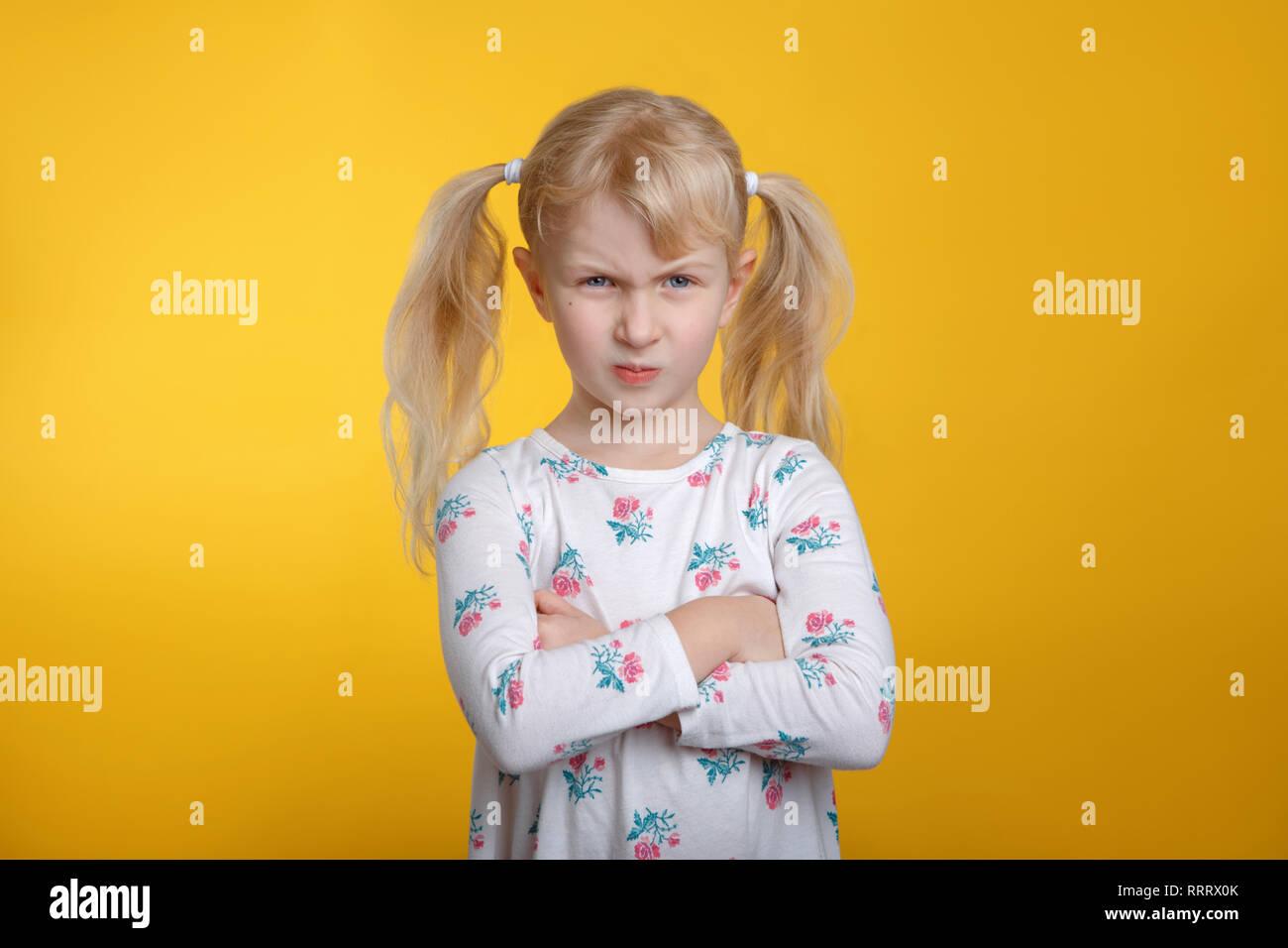 Jolie fille blonde caucasienne en colère grincheux aux yeux bleus en robe blanche posant en studio sur fond jaune avec les bras croisés sur sa poitrine. Kid enfant Banque D'Images