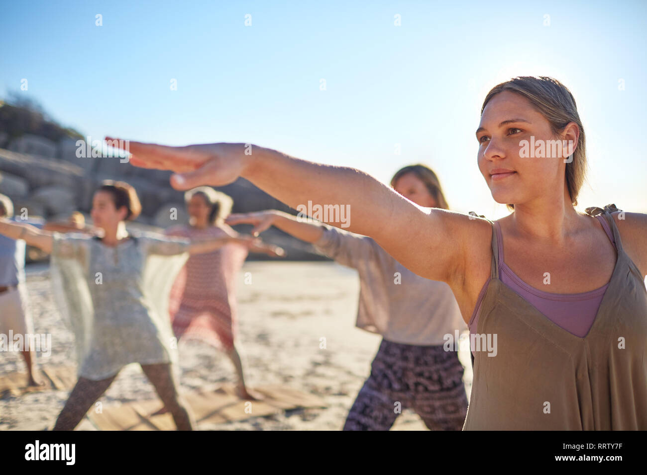 Certain woman practicing warrior 2 poser sur plage ensoleillée au cours de yoga retreat Banque D'Images