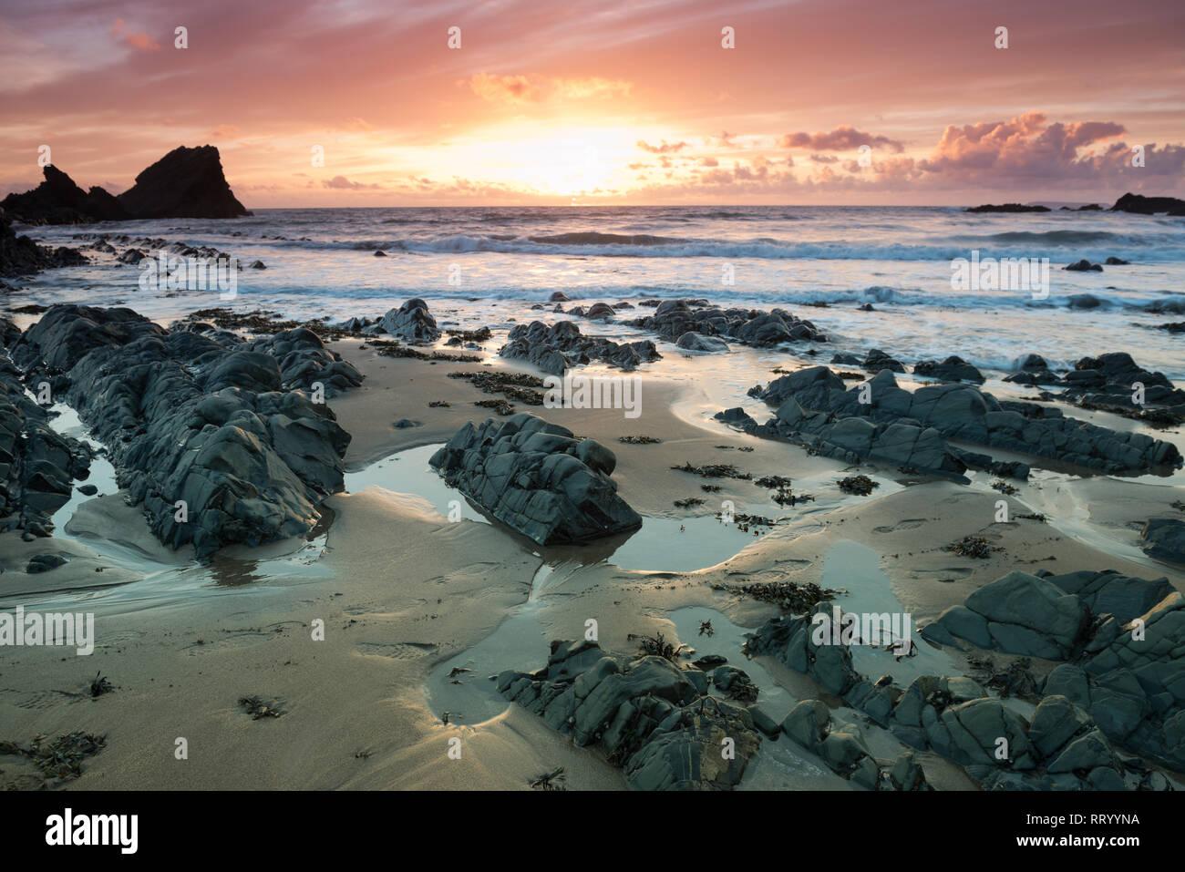 Coucher du soleil sur la plage de rochers à Hartland Quay sur la côte nord du Devon Banque D'Images