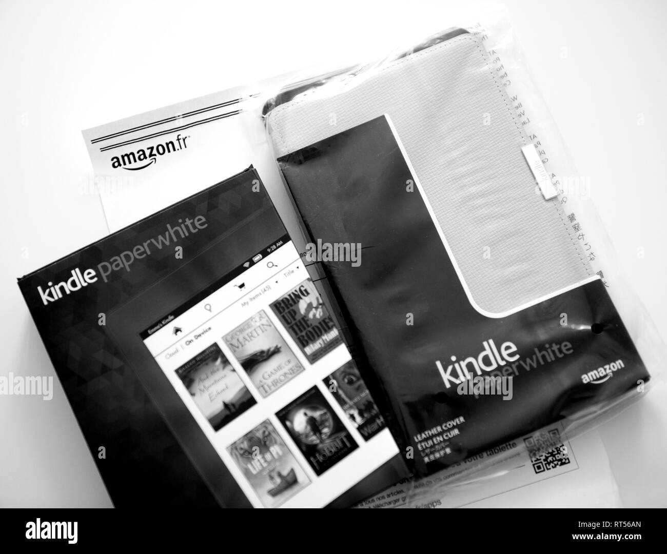PARIS, FRANCE - Mai 2016: Nouveau Amazon Kindle e-reader de sulfure dispositif électronique et sa couverture en cuir sur le papier A4 blanc et comprennent le prix de la facture Photo Stock