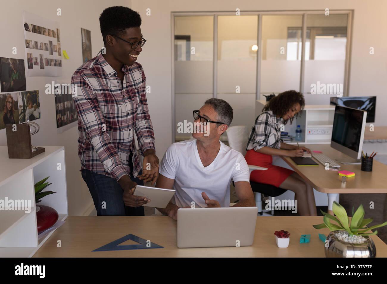Les cadres masculins au cours digital tablet at desk Banque D'Images