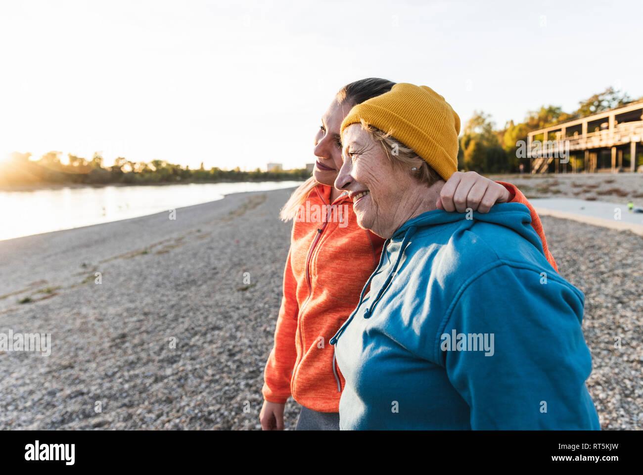 Fit grand-mère et petite-fille de marcher à la rivière avec les bras autour, s'amuser Banque D'Images