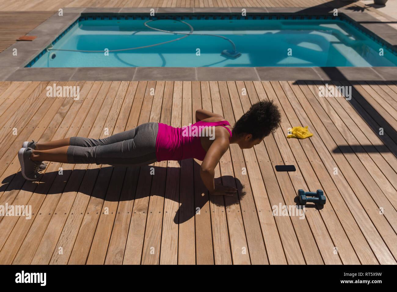 Woman performing push-up de l'exercice dans l'arrière-cour d'accueil Banque D'Images