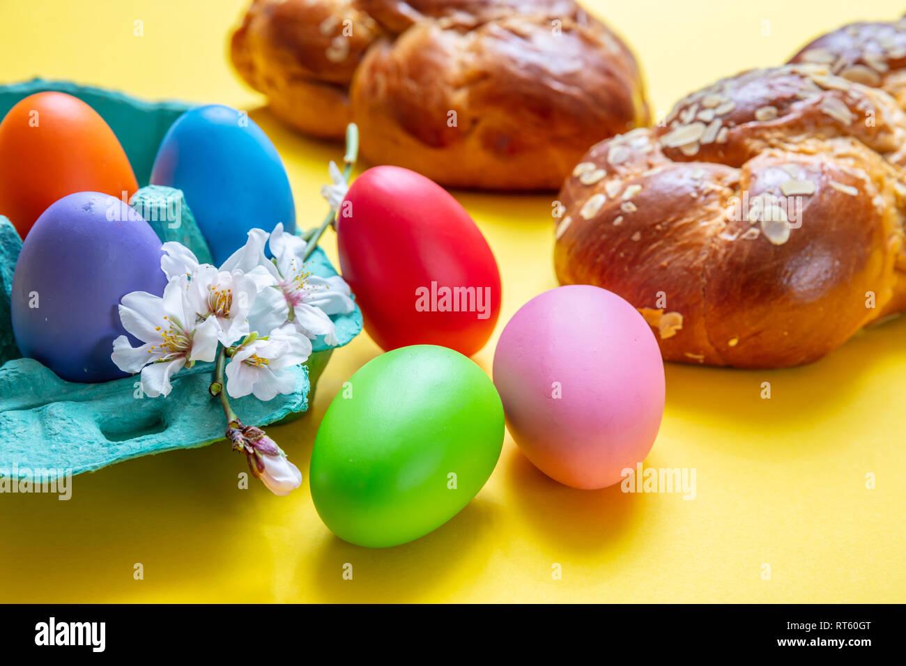 Œufs de Pâques et tsoureki tresse, pain sucré de Pâques grecque, sur un fond de couleur jaune Banque D'Images