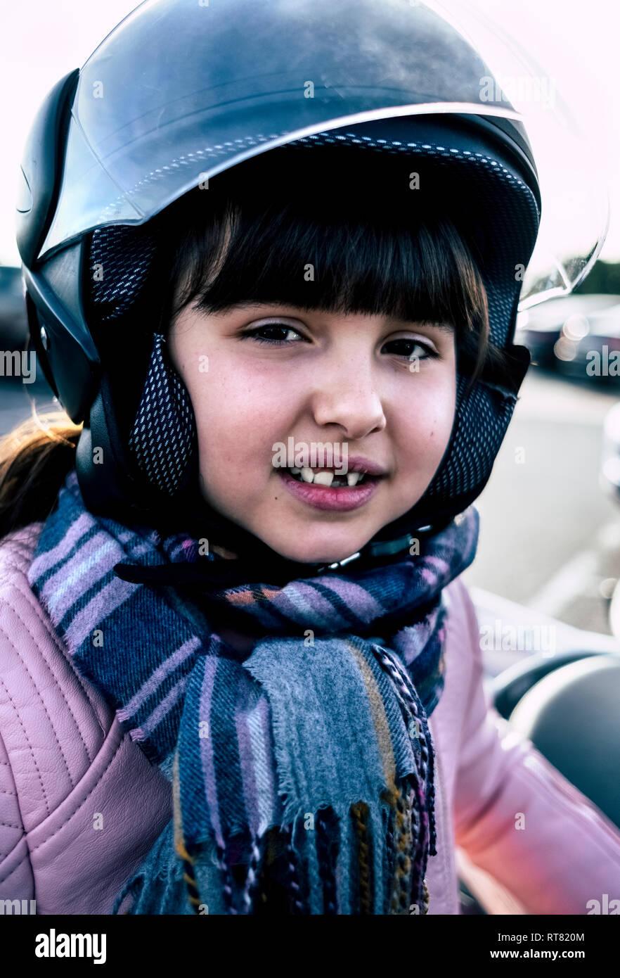 Portrait de petite fille avec écart de dent portant sur la moto casque Banque D'Images