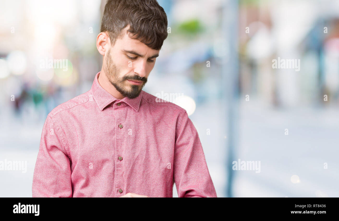 e7099e0112a7a Beau jeune homme portant chemise rose sur fond isolé Contrôle du temps sur  montre bracelet,