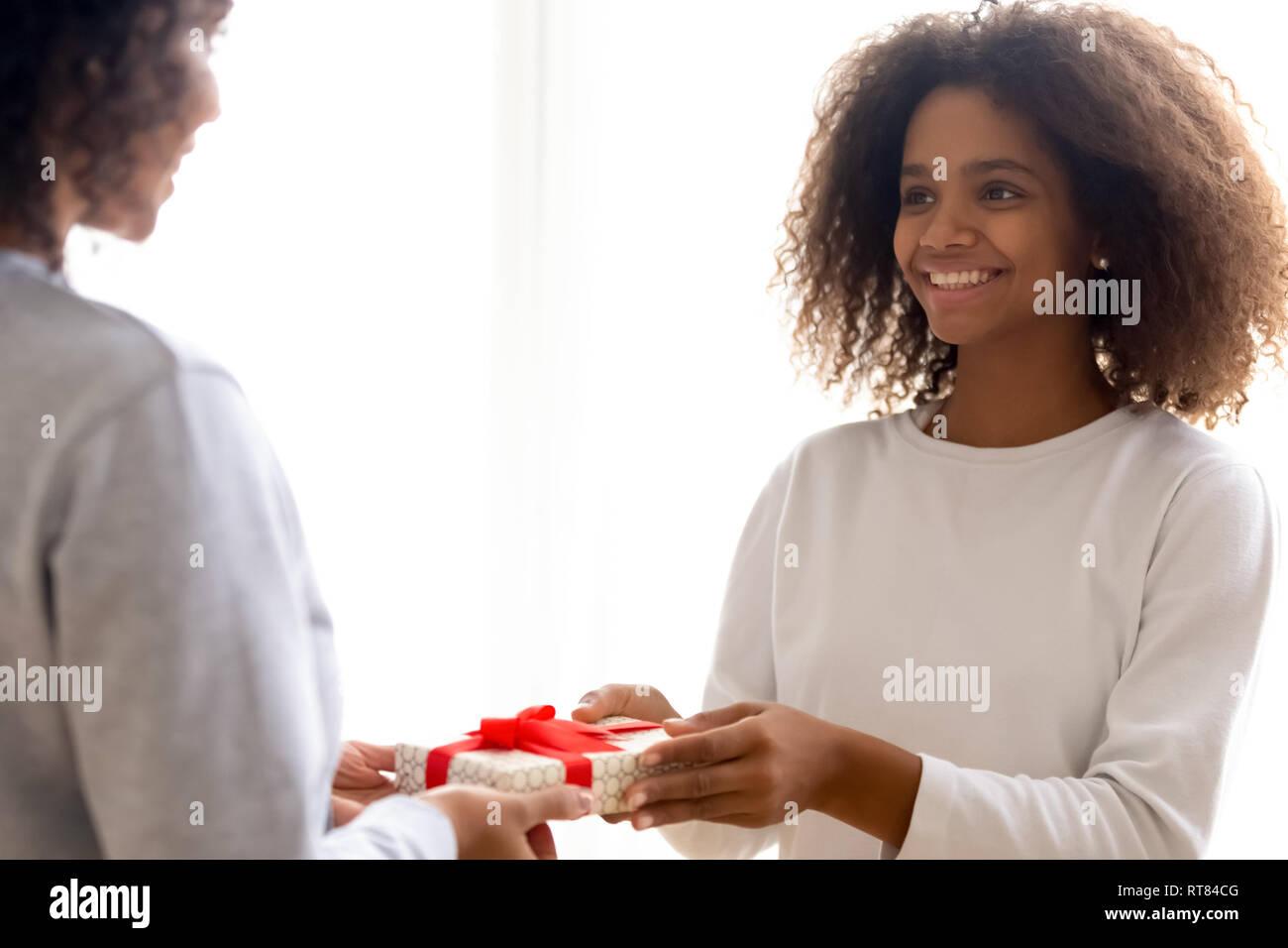 Happy mixed race fille donnant à présent Mère bien-aimée Photo Stock
