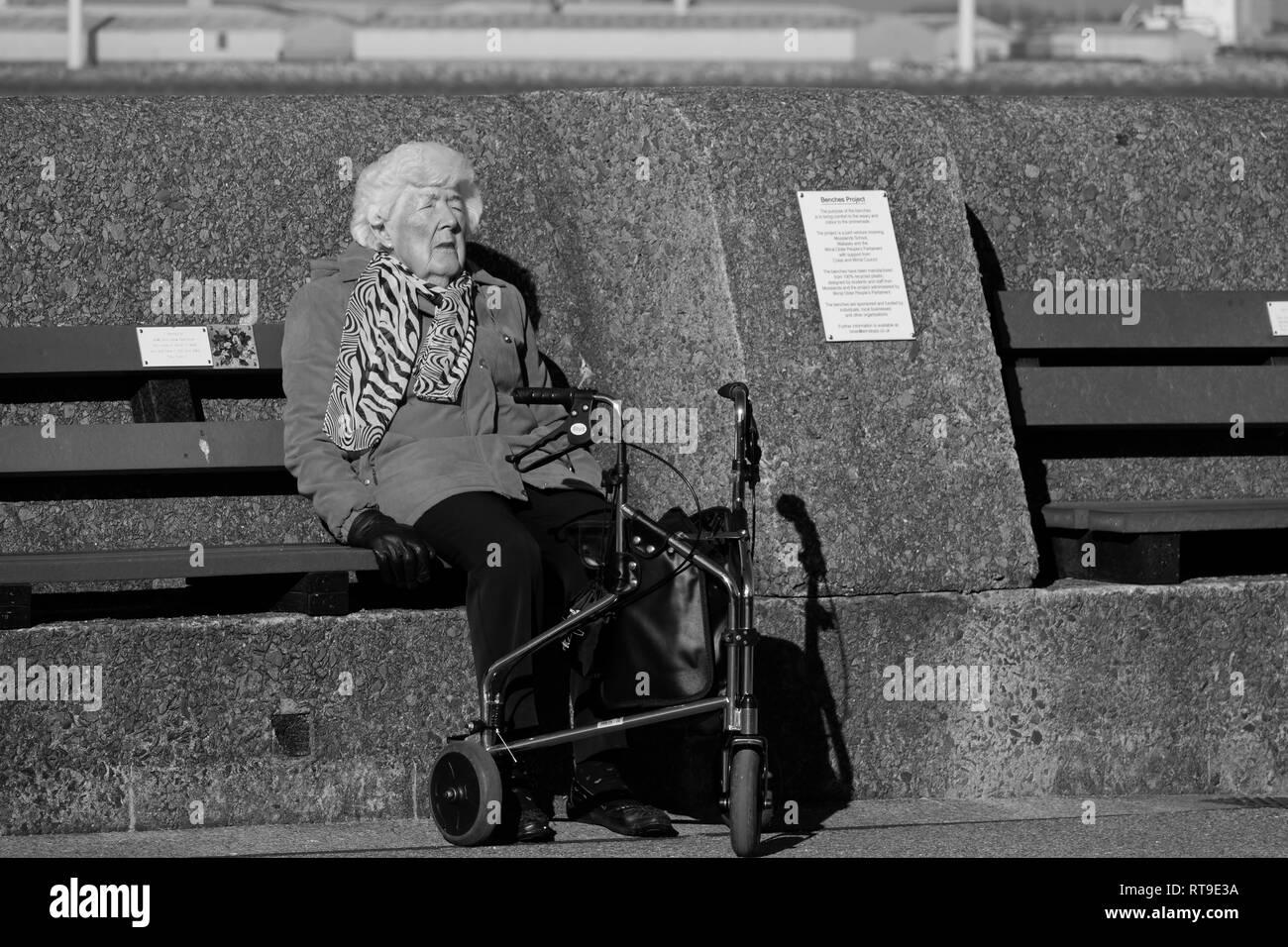 Image Monochrome d'une femme âgée avec une aide à la mobilité comme elle s'assoit sur un banc pour profiter du soleil au début du printemps Photo Stock