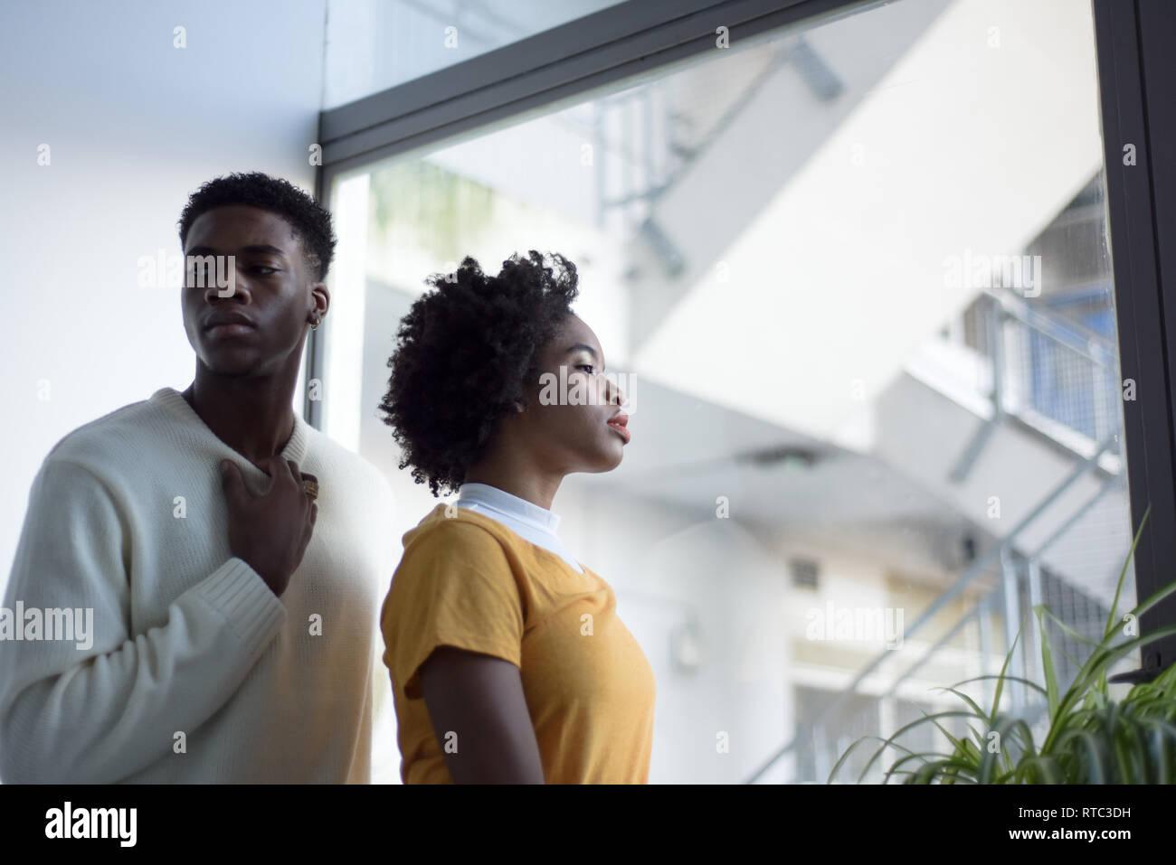 Un jeune couple noir attrayant à la recherche sérieuse dans une simple chambre blanche à la mode moderne, séance photo. Banque D'Images