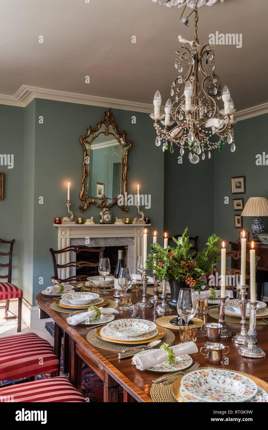 Table à manger en acajou avec des chaises capitonnées de Regency stripe avec cheminée en anglais Banque D'Images
