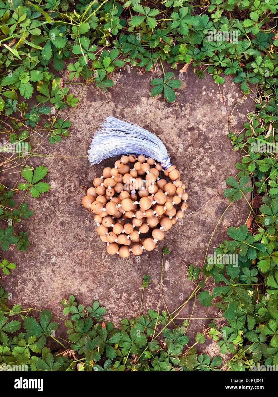 Chapelet en bois Tulasi reposent sur un fond de roche dans l'herbe verte. Japa Mala. Mantra. 108 perles. Banque D'Images