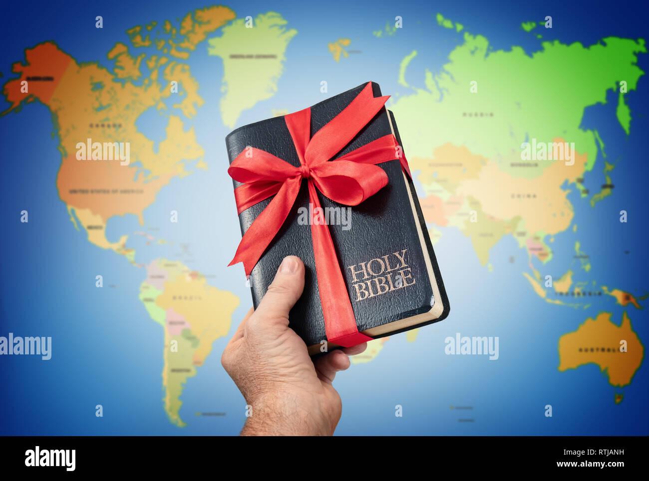 La Sainte Bible en main contre cadeaux carte du monde. Banque D'Images
