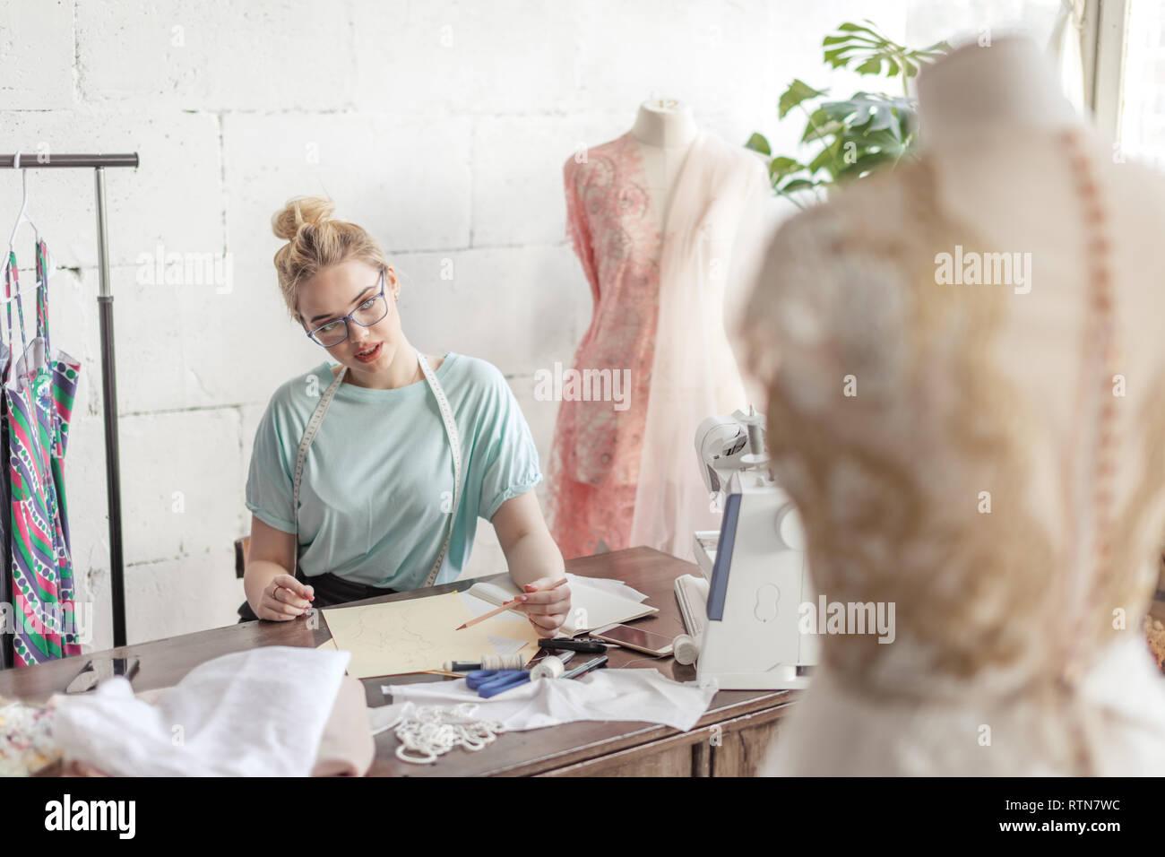 Créateur de mode sur mesure Belle de mesure se situe à dessin en milieu de travail ou de mettre par écrit les résultats après la mesure. Son studio est ensoleillée, pleine de colorf Banque D'Images