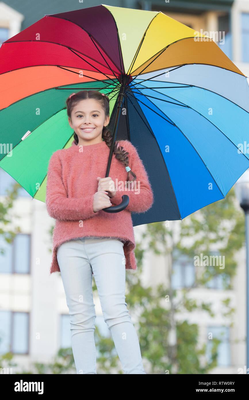 Petite fille cheveux longs avec parapluie. Accessoire coloré influence positive. Parapluie lumineux. Rester positif et optimiste. Tout mieux avec mon parapluie. Accessoires colorés pour l'humeur joyeuse. Photo Stock