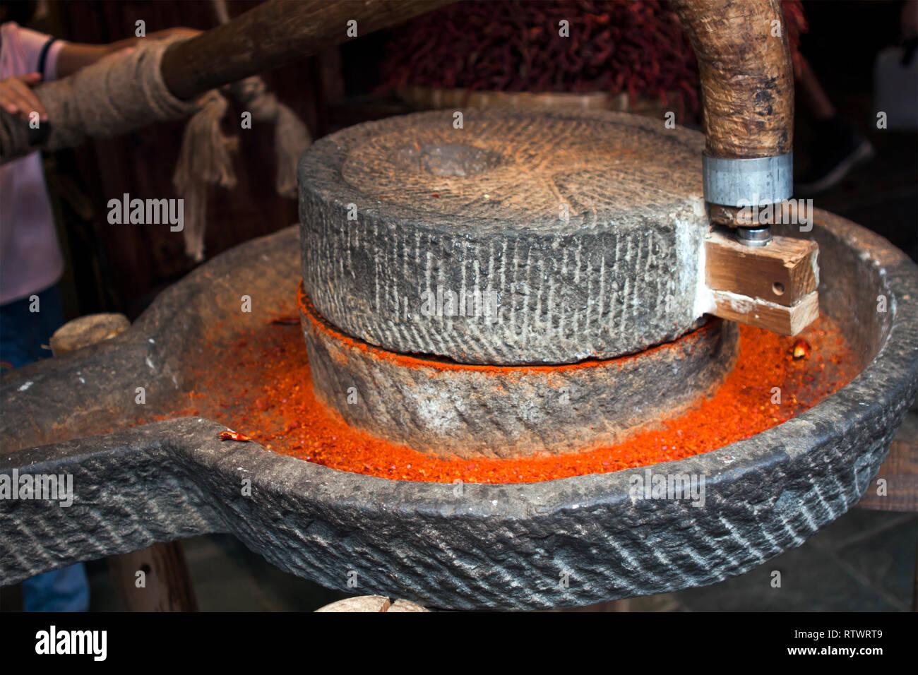 Piments rouges séchés de meulage à la main dans un moulin en pierre. Poudre de chili rouge au sol. Banque D'Images
