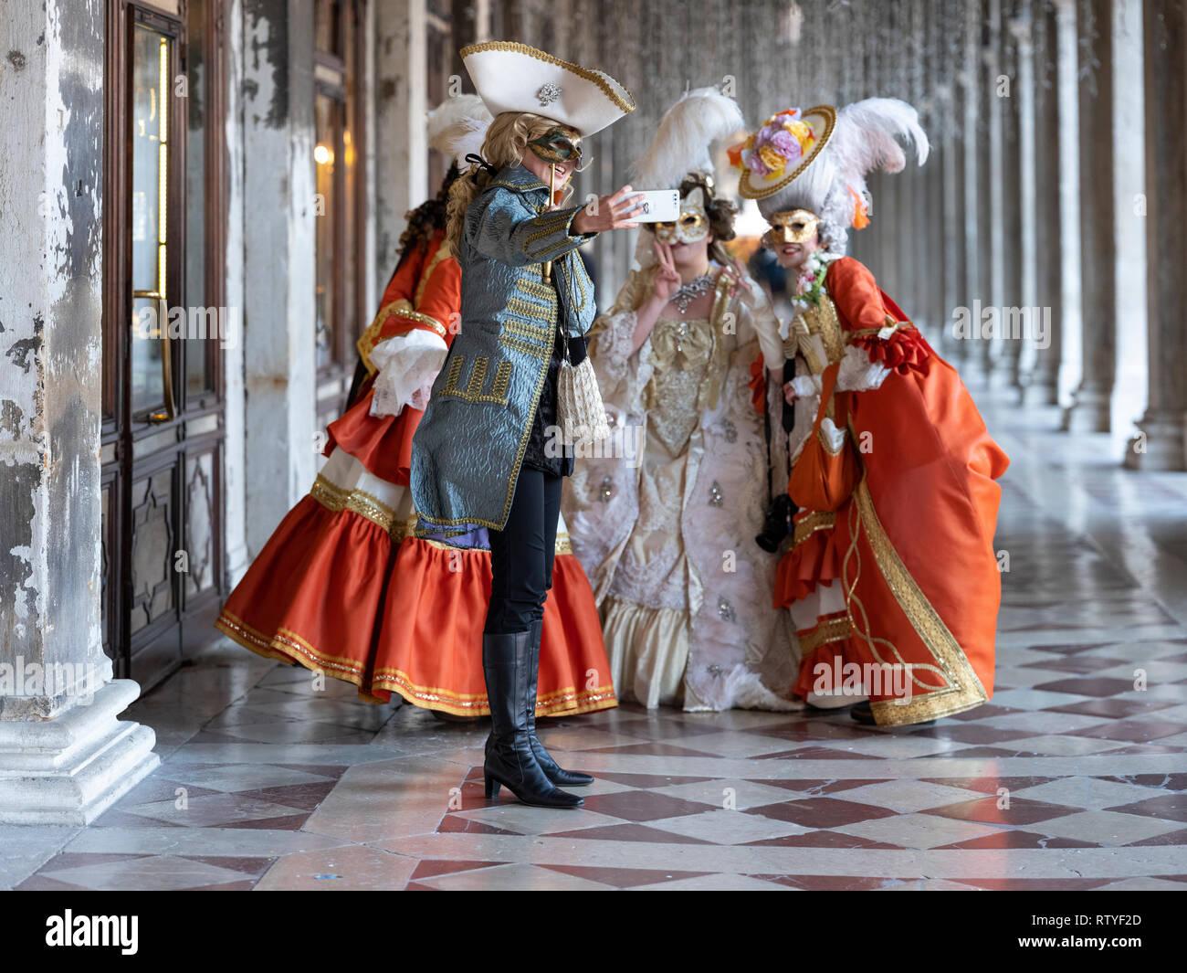 Un groupe de dames à la fête des masques de Venise ayant un groupe photographie prise avec un téléphone mobile Europe Italie Venise Banque D'Images