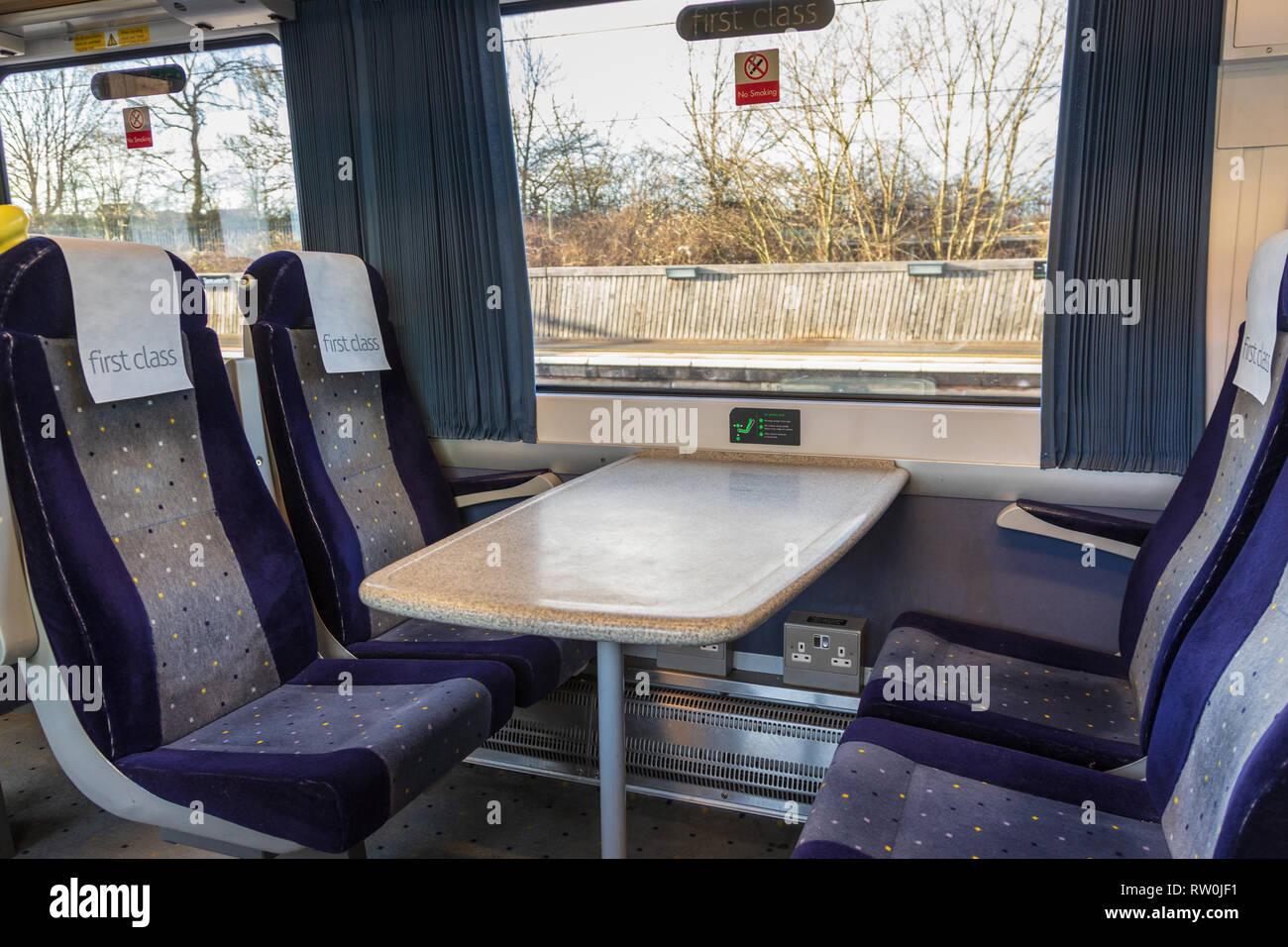 Première classe vide assis dans un train. Les quatre sièges bleu et le tableau sont à côté d'une fenêtre avec un signe de première classe Banque D'Images