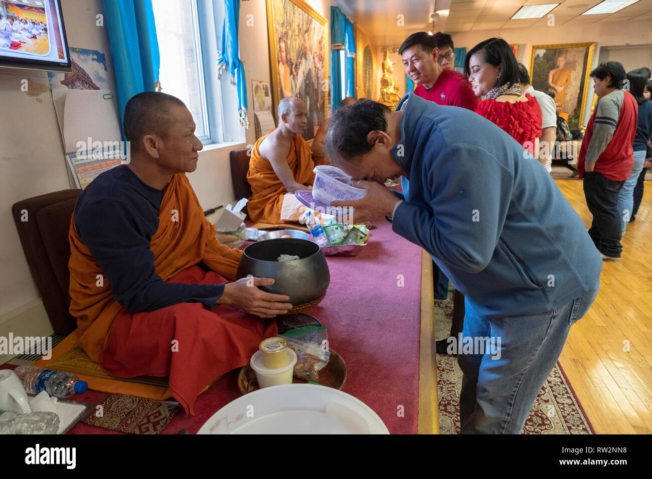Les fidèles bouddhistes fervents participer à l'ancien rituel de l'alimentation des moines. Dans un temple à Elmhurst, Queens, New York. Photo Stock
