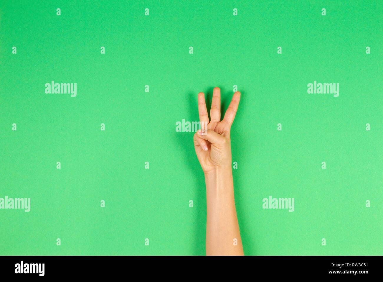 Kid part montrant trois doigts sur fond vert Photo Stock
