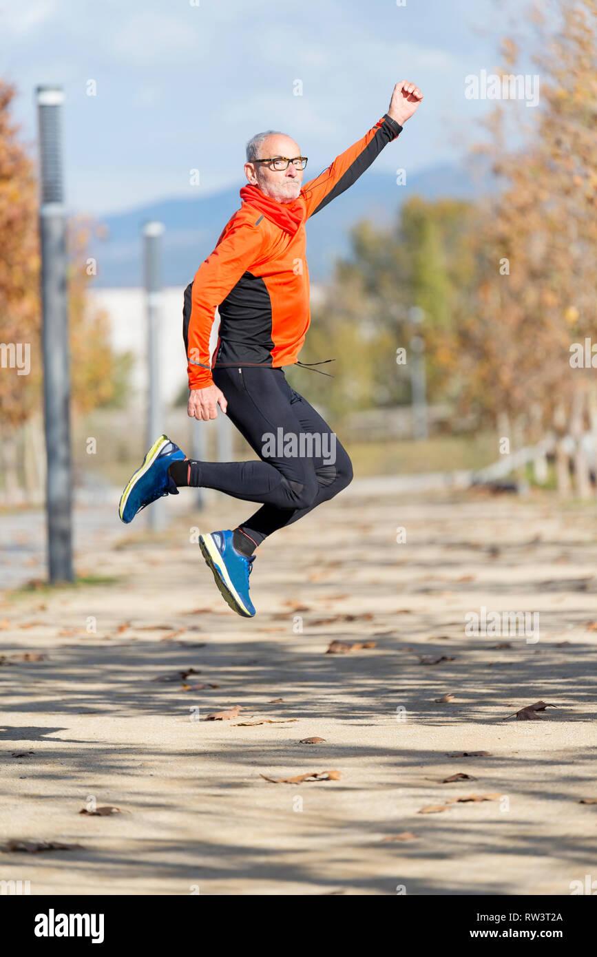 Un cadre supérieur runner man jumping les bras après l'exécution Banque D'Images