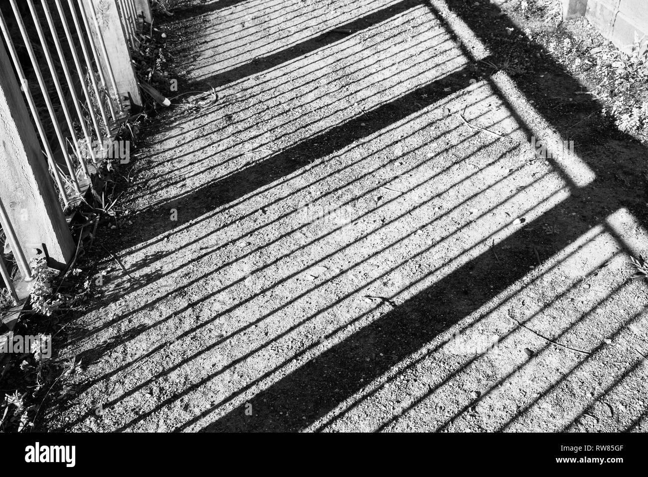 Point de vue intéressant sur les ombres fabriqué à partir d'une clôture sur un sol de gravier. Banque D'Images