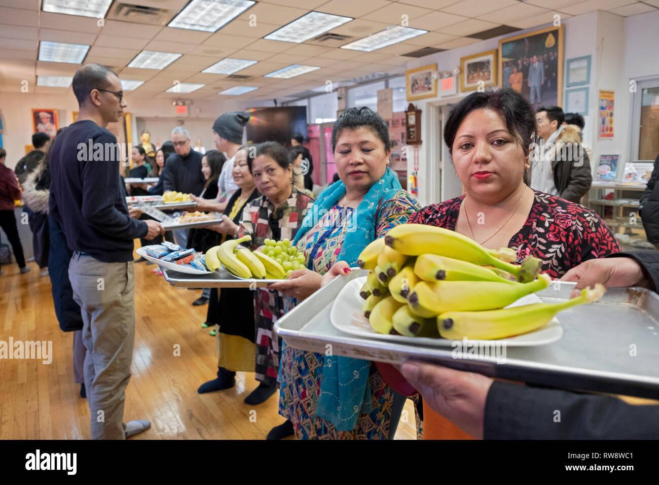 Fidèles à un temple bouddhiste forment une chaîne de montage d'offrir des aliments préparés et cuisinés pour leurs moines. Dans Elmhurst, Queens, New York Photo Stock