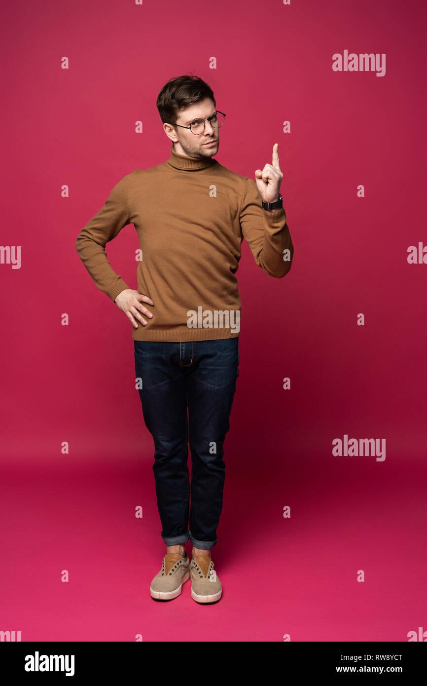 Bel homme comptant un avec les doigts sur fond bleu isolé. Photo Stock