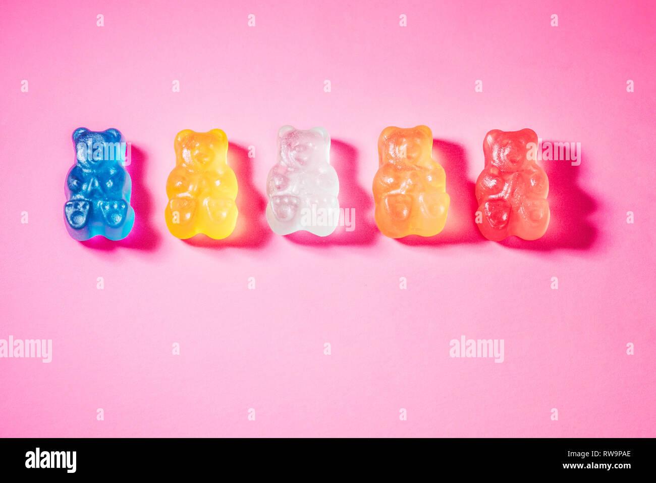Un close-up de cinq ours gommeux vivement colorées, photographié sur un fond rose avec poppy studio light. Banque D'Images