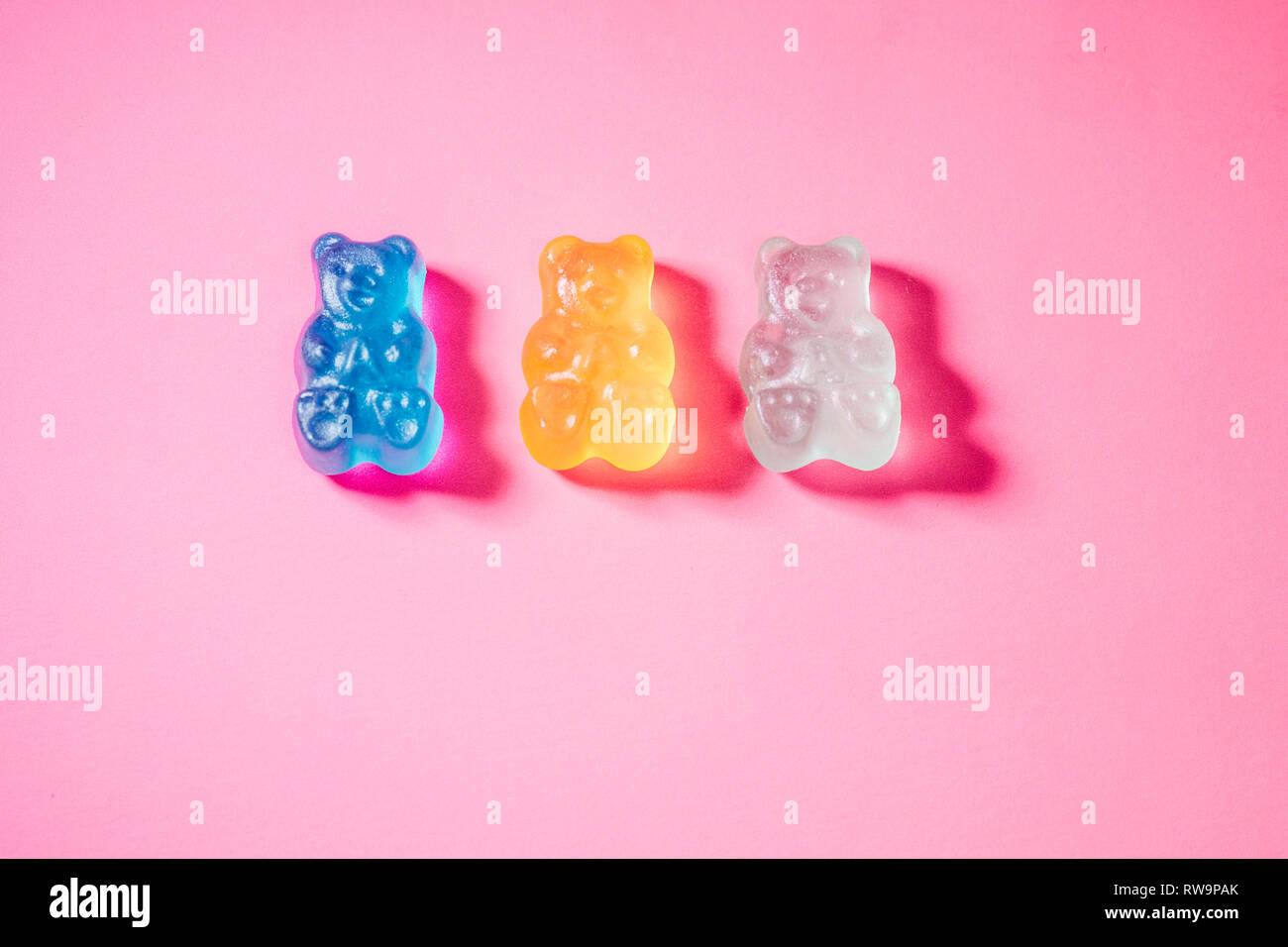 Un close-up de trois ours gommeux vivement colorées, photographié sur un fond rose avec poppy studio light. Banque D'Images
