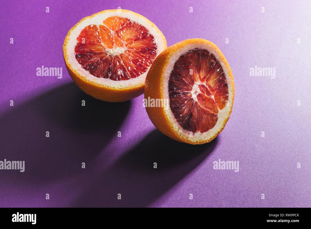 Un graphique de la vie encore une orange sanguine en tranches sur un fond coloré, photographiés avec la lumière et les ombres en studio. Banque D'Images
