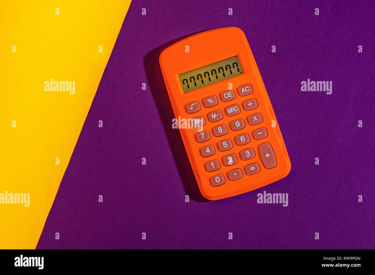 Un studio graphique photo d'une calculatrice d'orange sur un fond jaune et pourpre. Banque D'Images