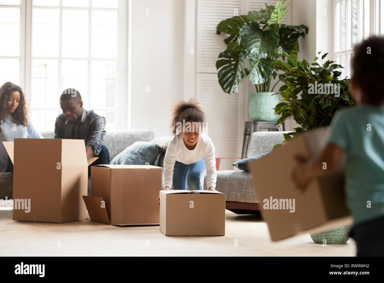 Peu d'enfants jouer avec des boîtes sur le jour du déménagement Photo Stock