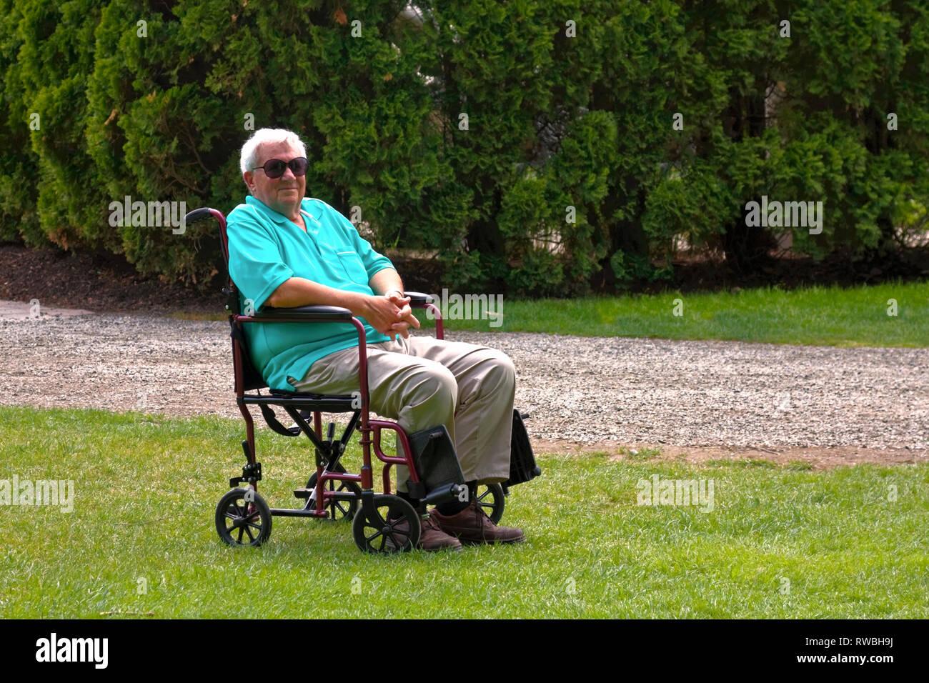 Man; fauteuil de transport; cheveux blancs; sourire; aide à la mobilité; l'attente; à l'extérieur, environnement naturel, horizontal; M. Photo Stock