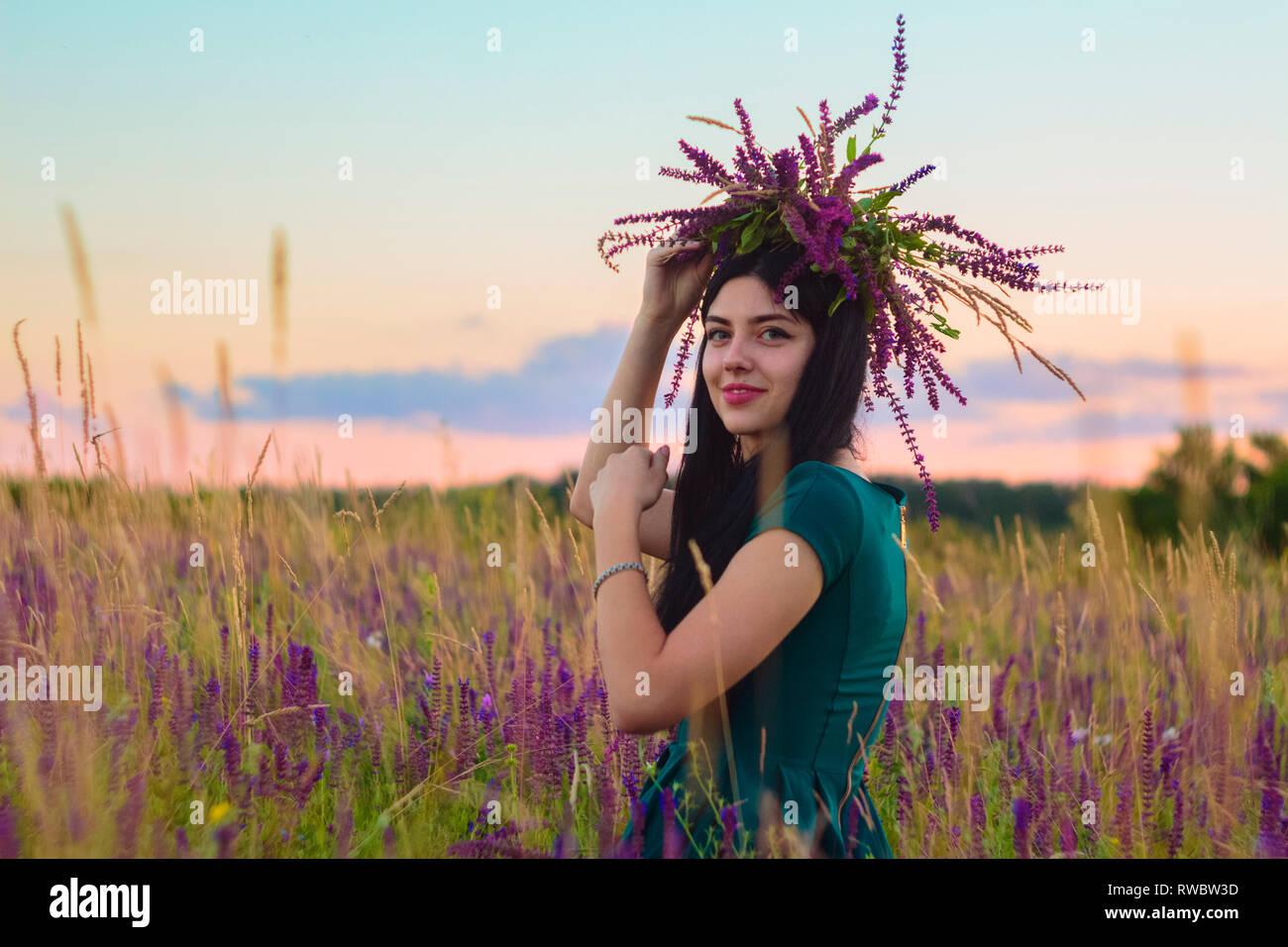 Beautiful happy brunette girl avec couronne dans les mains assis dans le champ de fleurs sur fond de paysage au coucher du soleil l'été en Ukraine. Banque D'Images