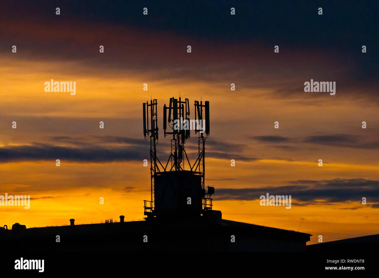 Site de la cellule sur le toit d'un bâtiment en silhouette Photo Stock