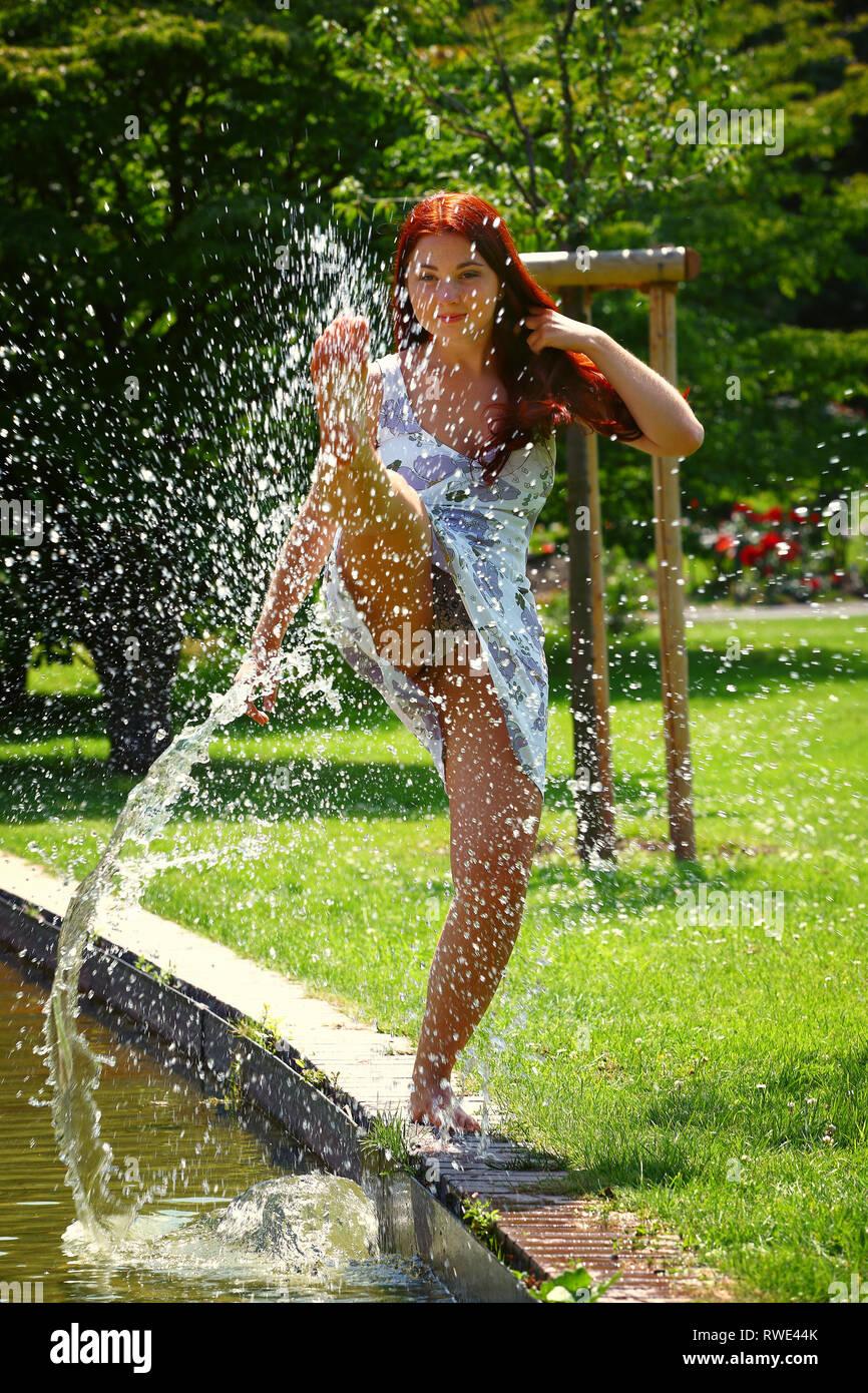 Une jeune femme crée une fontaine d'eau avec son pied à un étang dans un parc. Elle s'amuse et aime le beau temps. Banque D'Images