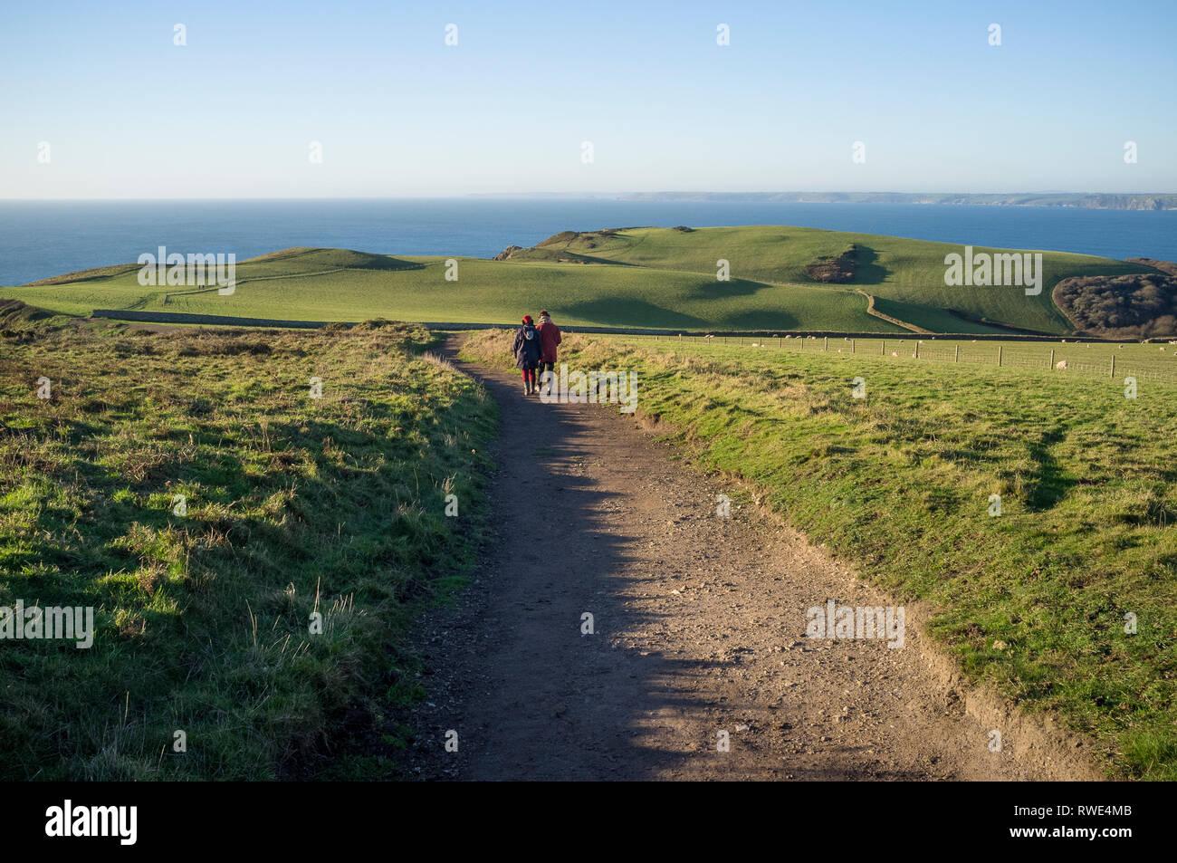 Les Amis à marcher le long de la pointe de la queue, un spectaculaire promenade côtière de Bolberry jusqu'à Hope Cove sur la côte sud du Devon, UK Photo Stock