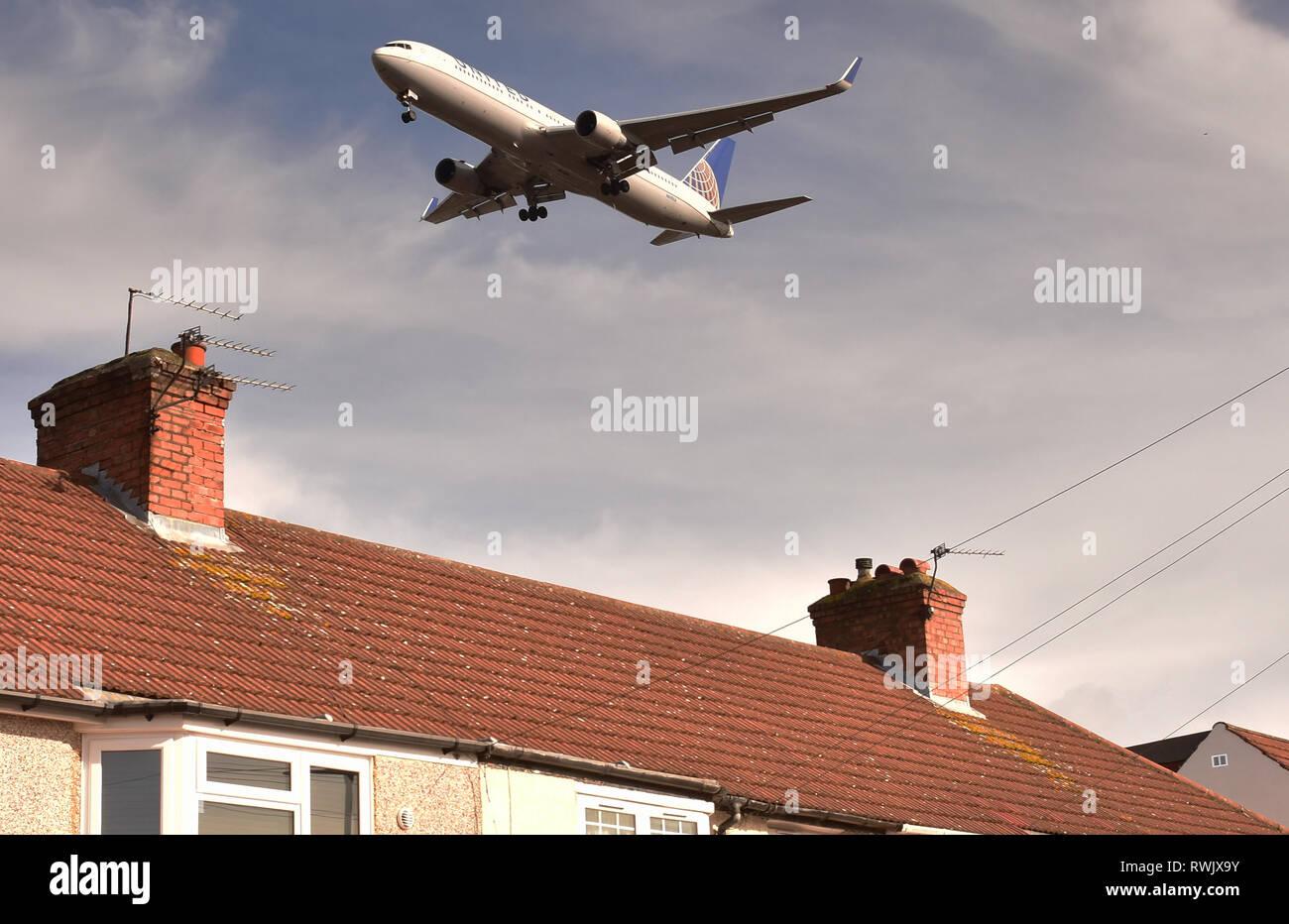 Les aéronefs volant à basse altitude, à l'atterrissage à l'aéroport de Heathrow, Londres plus de maisons Photo Stock