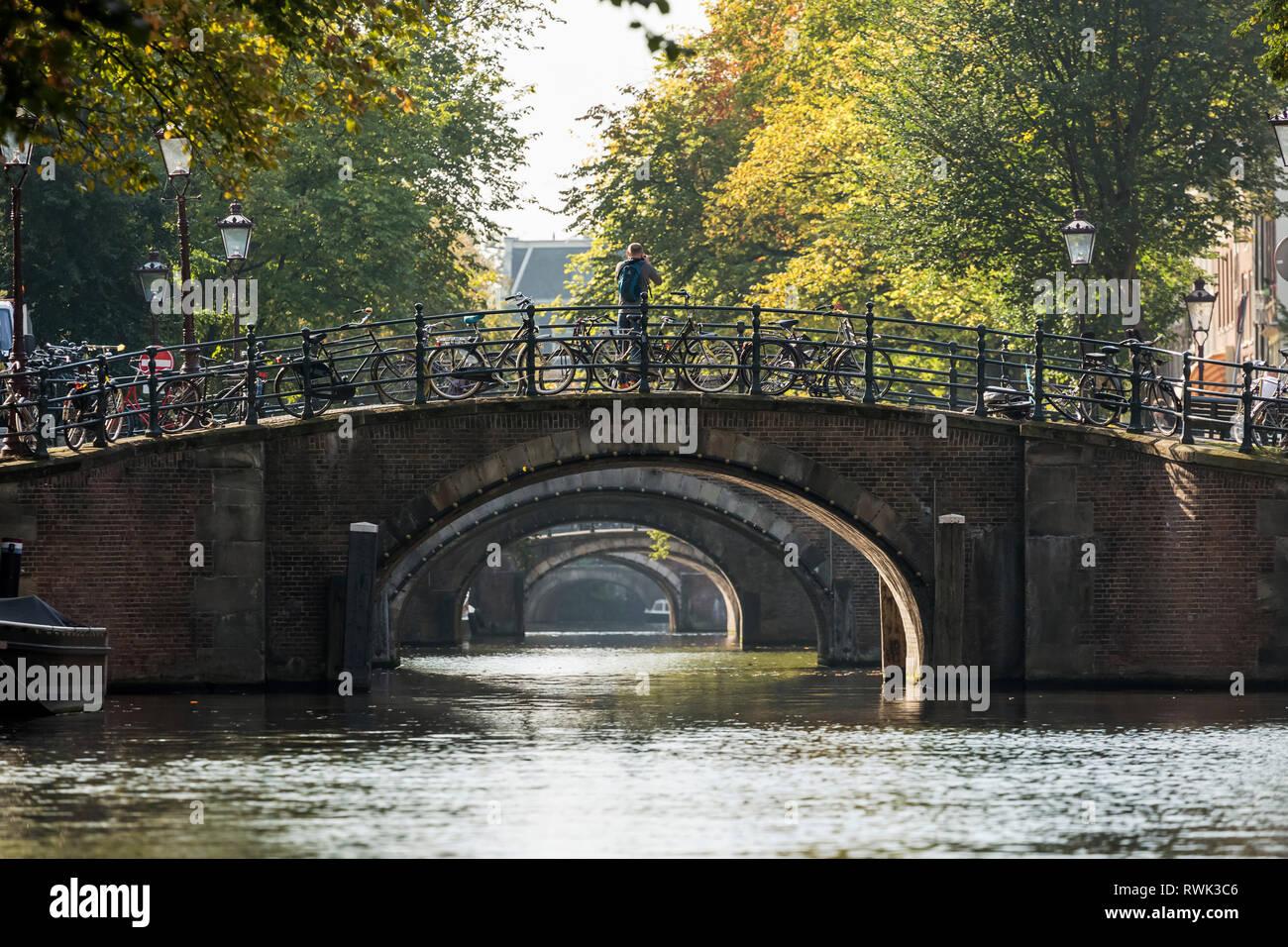 Plusieurs moyens de passage de pont en pierre le long d'un canal avec plusieurs motos sur main courante; Amsterdam, Pays-Bas Banque D'Images