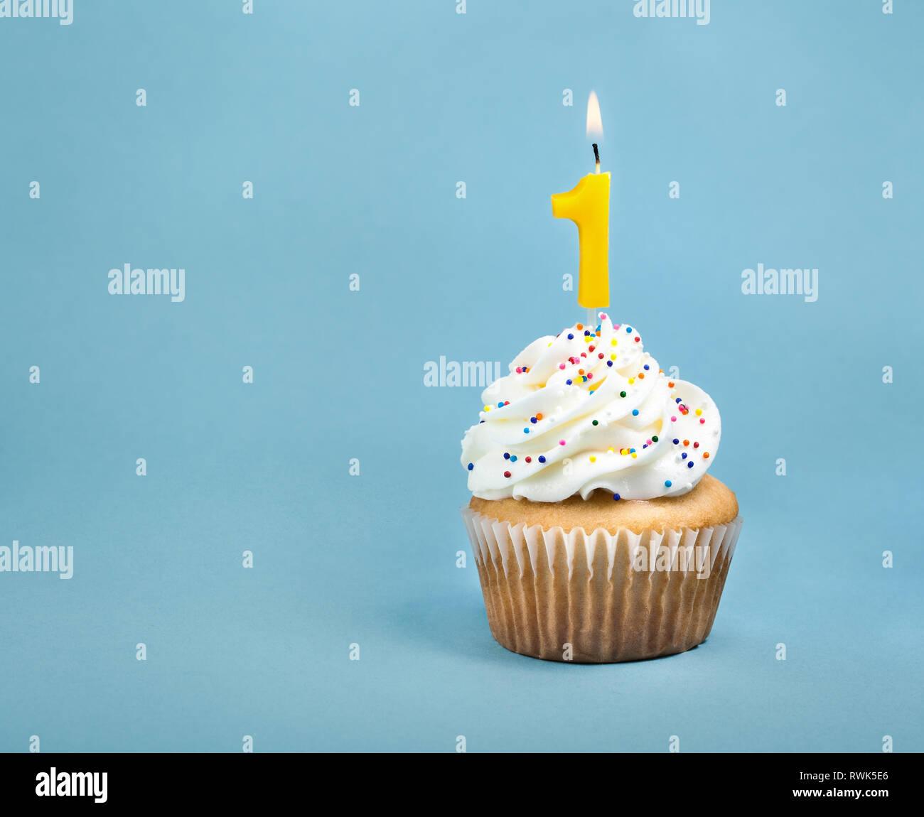 Un anniversaire cup cake avec glaçage buttercream, arrose et un numéro un allume bougie d'anniversaire. Photo Stock