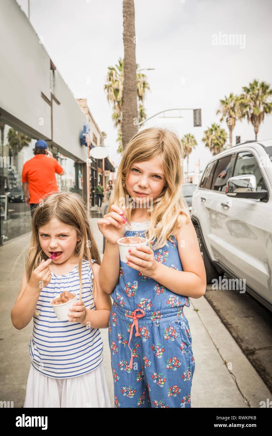 Fille et soeur de manger la crème glacée sur trottoir, portrait, Los Angeles, USA Photo Stock